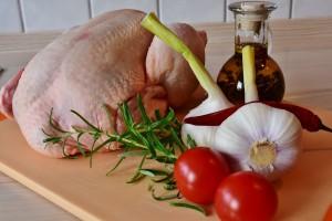 oczyszczony zdrowy drób leżący na desce w towarzystwie czosnku i pomidorków.