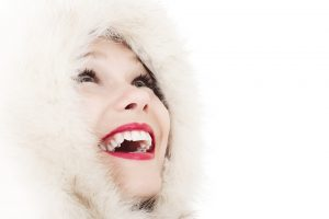 uśmiechnięta kobieta otulona futrzanym kapturem
