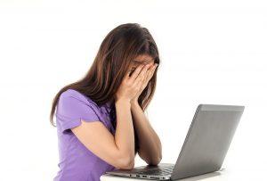 źródło: pixabay.pl załamana kobieta siedząca przed laptopem z twarzą schowaną w dłoniach nie wie jak ma zwalczyć zmęczenie i senność