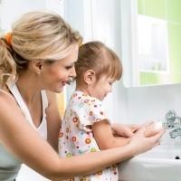 Mama uczy córkę myć ręce aby zmniejszyć podatnośc na infekcje tak jak groprinosin