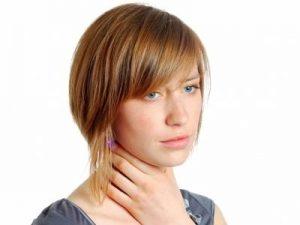 młoda kobieta trzyma się za gardło ponieważ ją boli. potrzebuje inovox pastylki