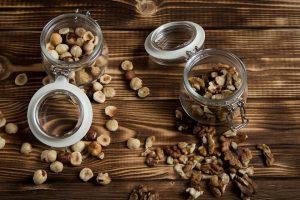 łuskane różne rodzaje orzechów na drewnianym blacie i szklanych pojemnikach