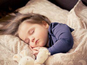 obniżona odporność u dziewczynki śpiącej w beżowej wzorzystej pościeli w granatowej piżamce i przytulanką